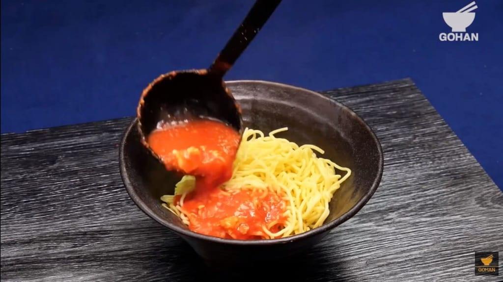 麺にトマトをかけている