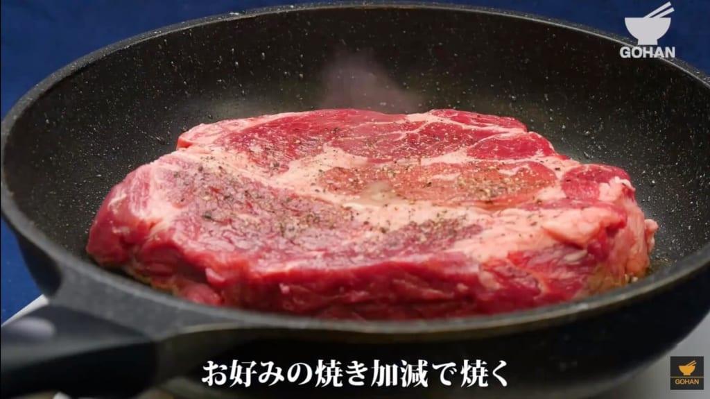 ステーキ肉を焼いている