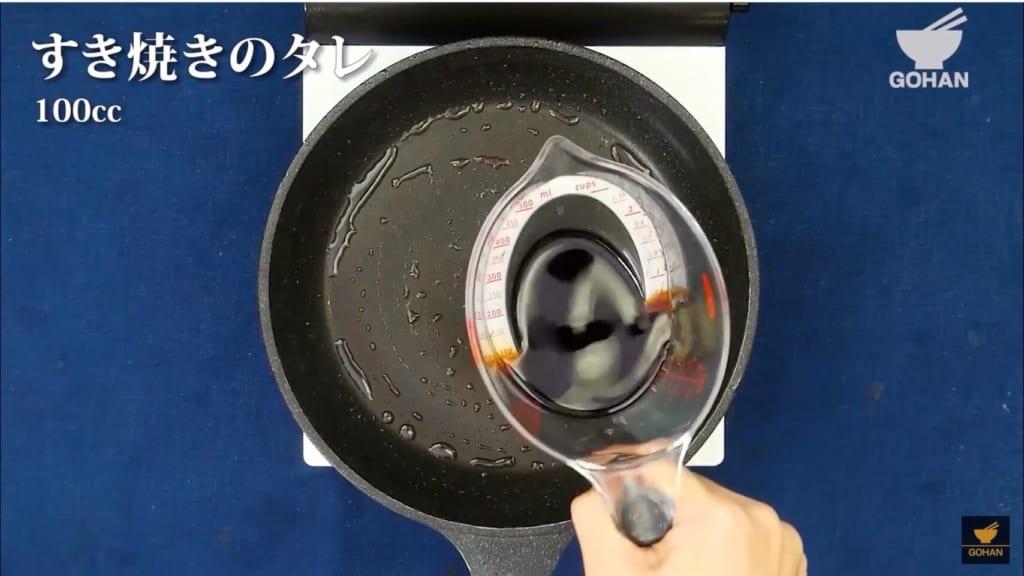 フライパンへすき焼きのタレをいれている