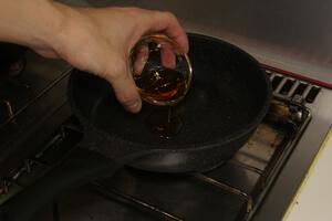 フライパンにごま油を入れている