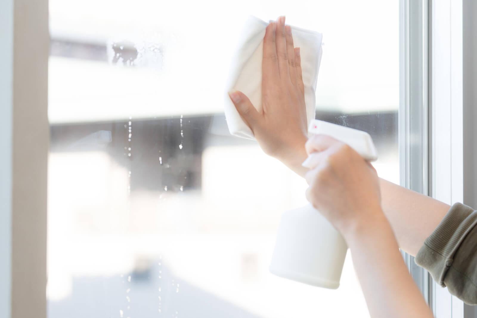 雑巾で窓を拭いている
